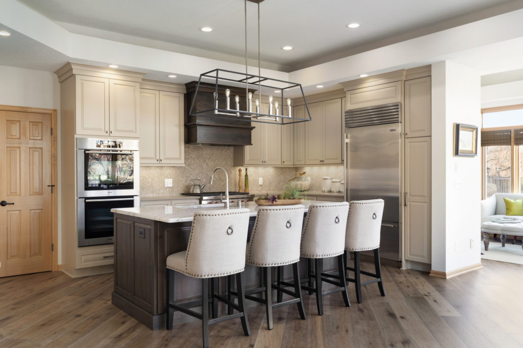 A newly remodeled kitchen with an island accompanied by four chairs.